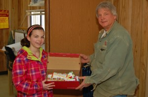 Hambright third-grader Jenna Breightback gives a box of treats to Shake Spitler, MCA Construction supervisor.