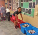 Student Aja Brown tries to figure out how many glue sticks, pens and markers Central Manor collected this year.