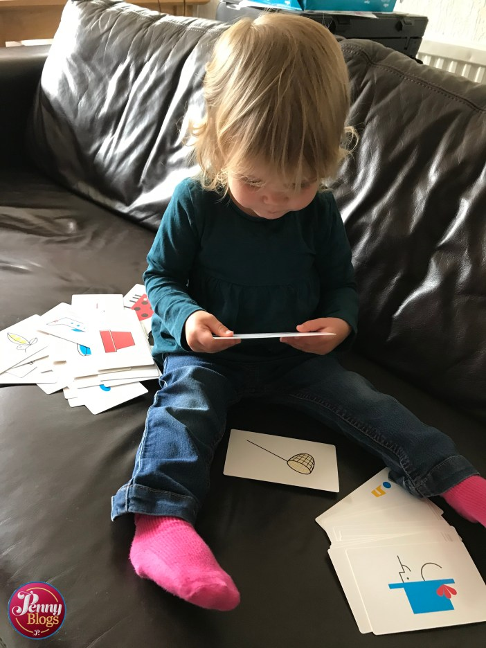 A small girl with blond curly hair and a sea green top sat on a leather sofa working her way through a pile of flash cards