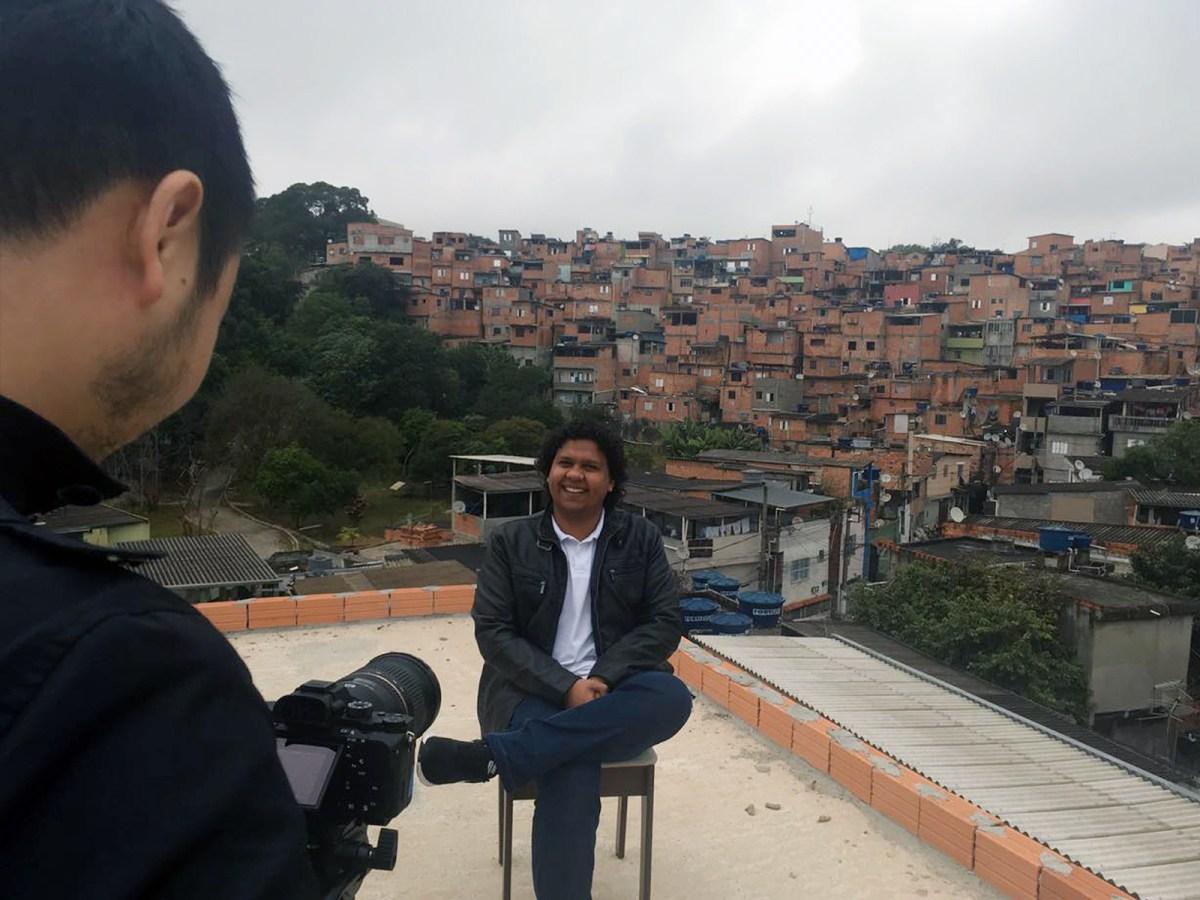 Imagem mostra jovem sentado durante gravação do episódio Empreende Aí. Ao fundo, bairro periférico