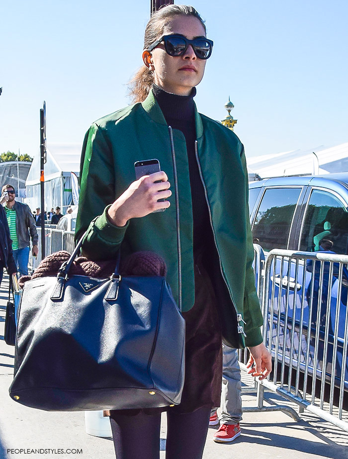 How to wear green bomber jacket, turtleneck, brown mini skirt, Prada tote bag, Celine sunglasses and biker boots. Model off duty look, street style fashion Paris, what to wear now, girl with iPhone