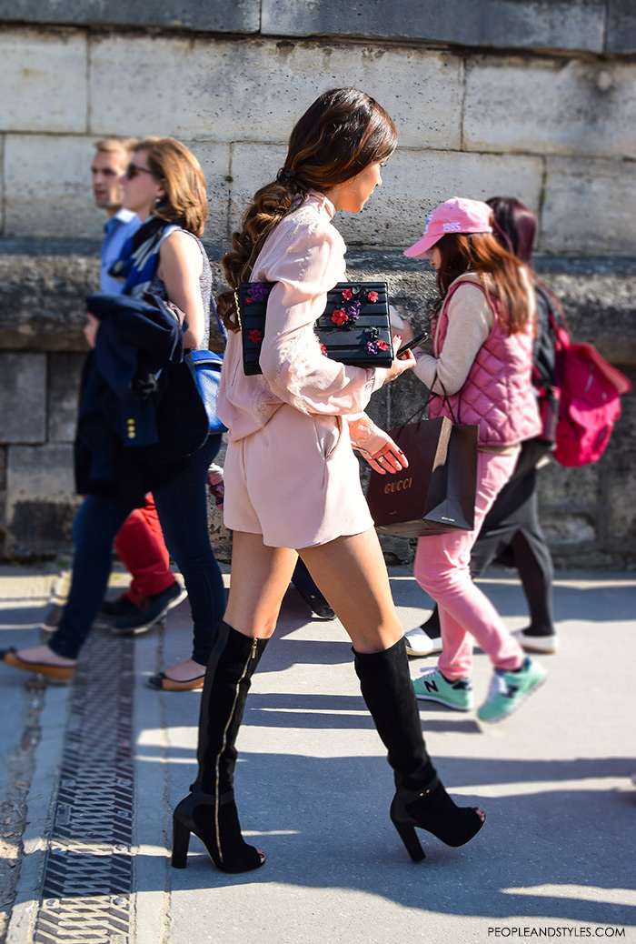 Stylish outfit of popular fashion blogger Nergin Mirsalehi wearing pink jumpsuit and open toe black knee-high boots in Paris during Paris Fashion Week