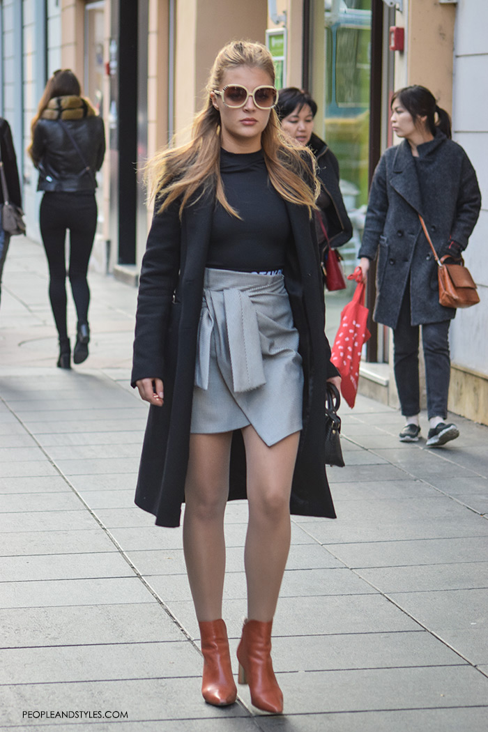 Peopleandstyles. What to wear. Culottes. This street stunner styled well her wrap mini skirt and ankle boots keeping the look elegant with a black clean line coat and a black bodysuit.