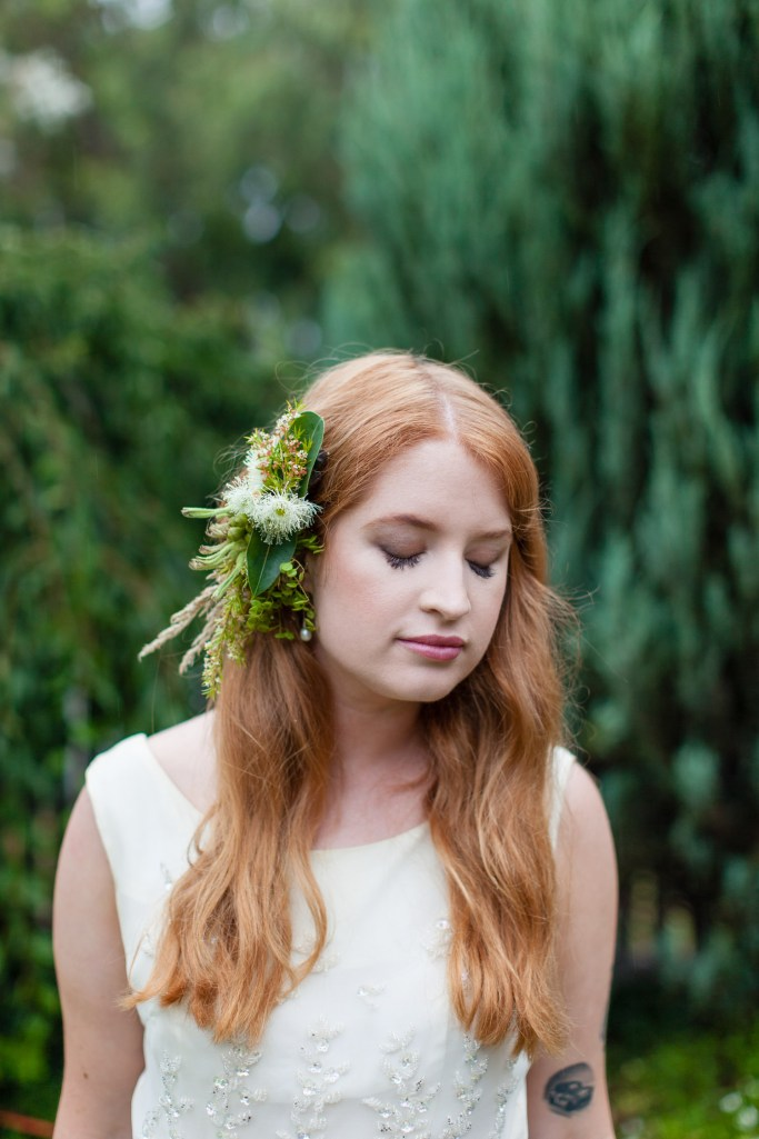 Brides beautiful red hair contrasts perfectly with native flower comb and background greenery photographed by Melbourne wedding photographers Pepperberry Photography.