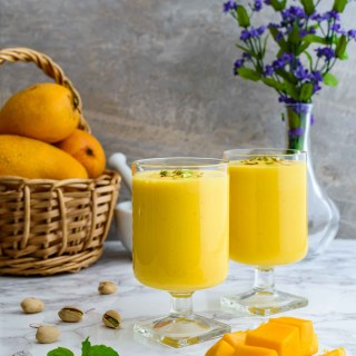 A horizontal shot of mango lassi decorated with pistachios and saffron.