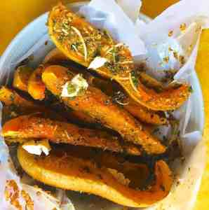 Slices of orange coloured baked squash in parchment paper placed on a pale blue dish, and garnished with fresh herbs and parmesan cheese.