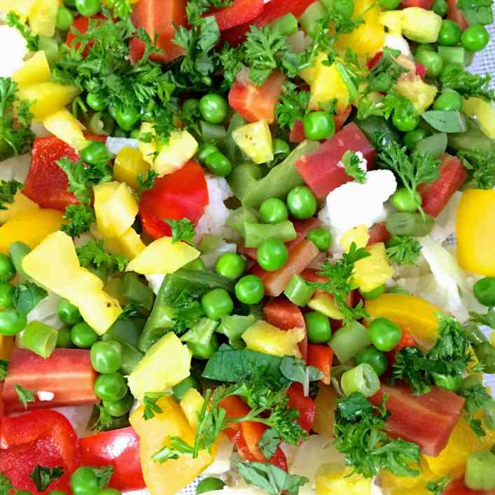 Brightly coloured green, red, yellow and white slices of vegetables in a baking dish, ready to bake