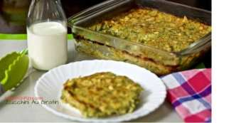 A slice of zucchini au gratin on a white plate, with. a glass dish of au gratin in the background and a checked white and red napkin on the side. A bottle of milk seen in the background