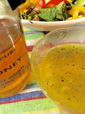 Bottle of honey next to a bowl of honey lemon garlickly salad dressing