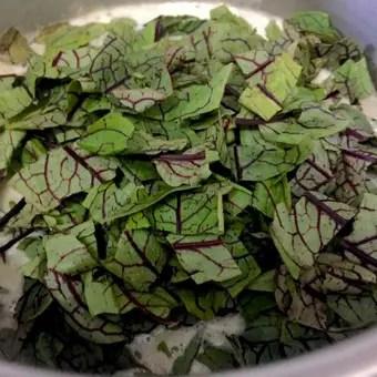 Add sorrel leaves to bean sorrel soup_PepperOnPizza.com
