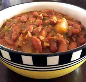 Nutritious tasty Rajma Masala Curry -spiced red kidney beans in tomato onion gravy in a yellow bowl with a black and white checked border