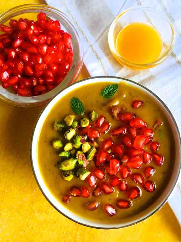 A bowl of pumpkin soup of roasted pumpkin curried with Indian spices, garnished with pomegranate and pista nuts and with a cup of orange juice on a white napkin and a bowl of pomegranates alongside