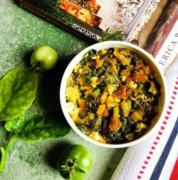 A bowl of greens - saag of radish greens spinach curry with green tomatoes and a white red black napkin and a book on food on a green background