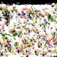 Step 2 in making Flavoured butter: Spread Butter on the flowers and herbs and sprinkle more edible flowers on top