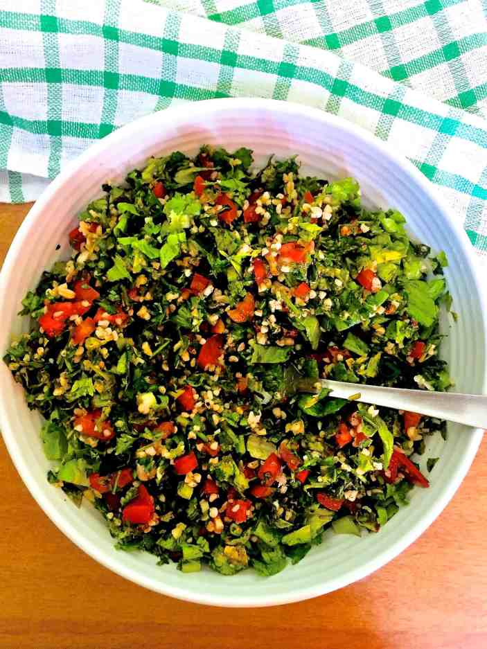 Red and green colourful Levantine Tabbouleh in a white bowl with a green and white checked napkin on an orange background. Finely chopped Green flat leaf parsely, red tomatoes, white creamy bulgar, green romaine lettuce
