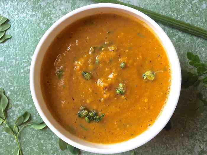 A large white bowl filled with orange mustard moringa pods leaves carrot and corn soup. On a light green background. with a drumstick above and moringa leaves alongside. Garnsihed with fried moringa blossoms