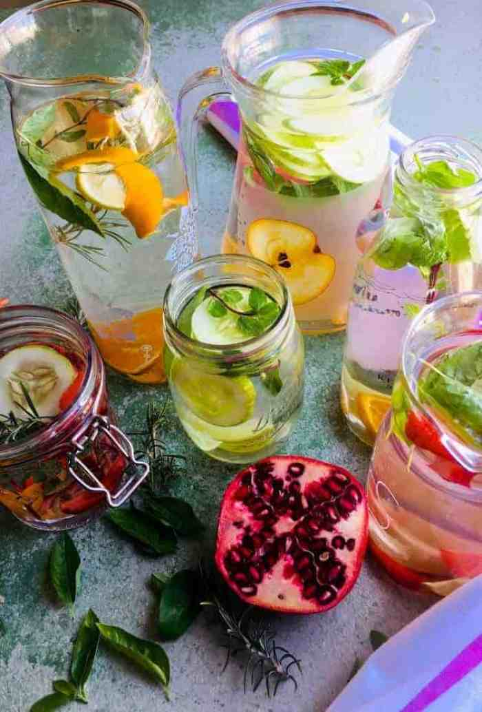 Glass jars and bottles with colourful fruits and herbs in water for naturally flavoured water made at home. Strawberries, cucumber, orange and lemon in combination with basil, mint and rosemary