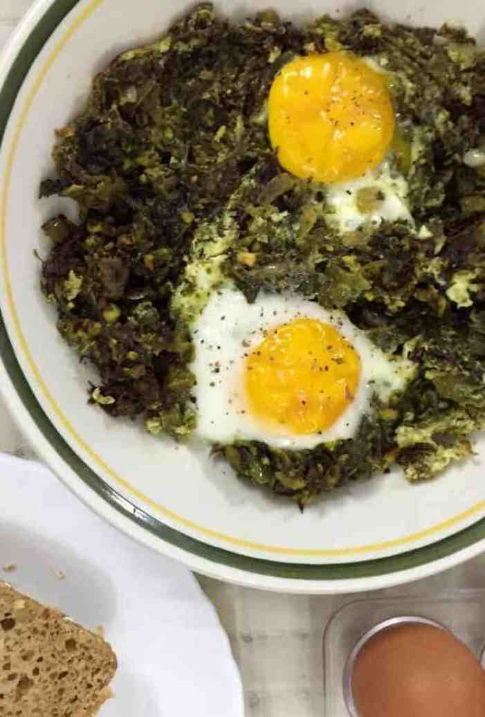 Green Kale Shakshuka with the cooked kale spread on a white plate with a green and yellow edging. Two eggs with their yolks resting on the kale