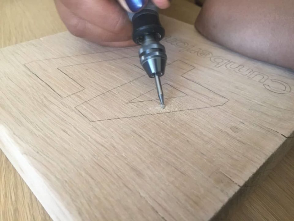 Closeup photo of the Dremel multi-tool being used to engrave a house number into a piece of basswood