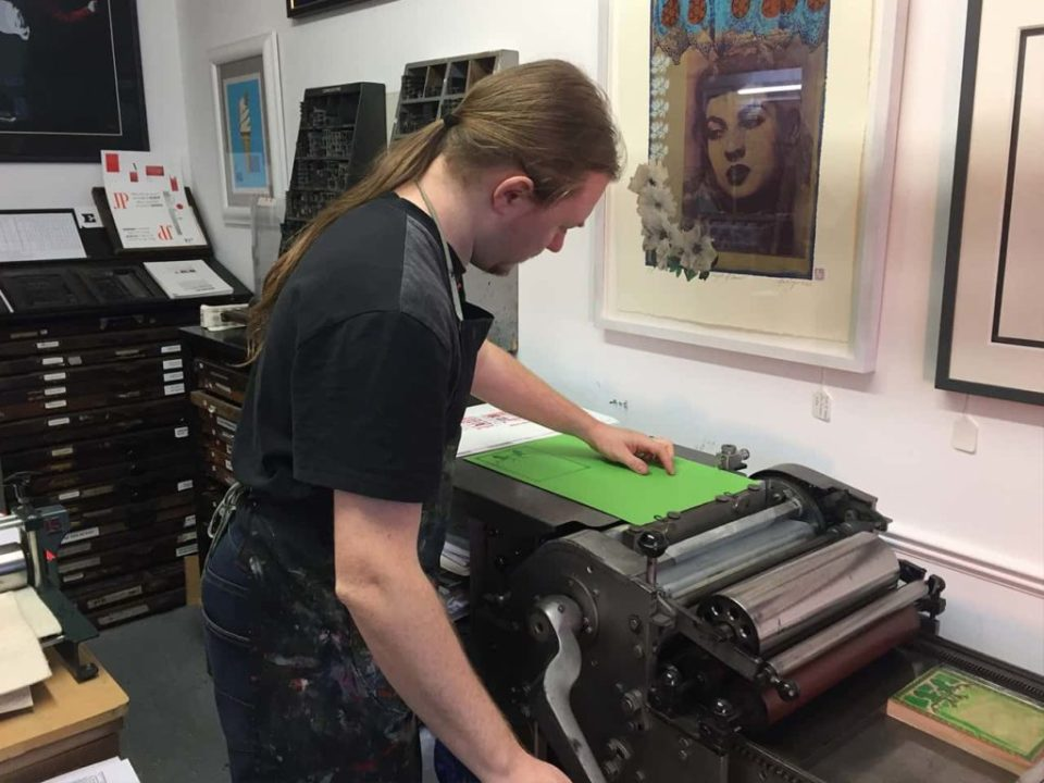 Operating a letterpress print machine printing christmas cards onto green card