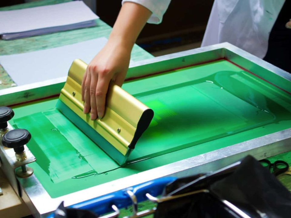 A metal silkscreen printing frame using green ink to print a design by hand