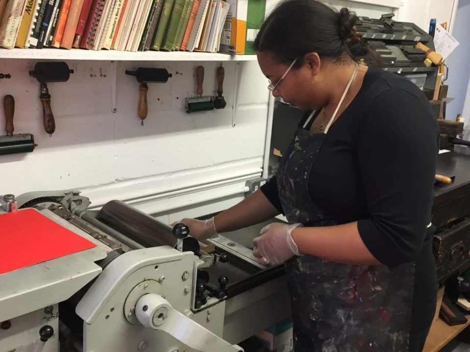 Operating a letterpress print machine. Printing handmade christmas cards