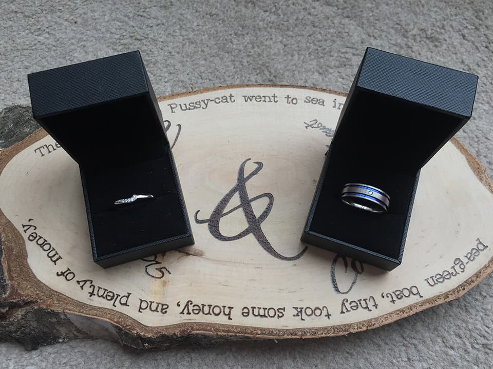 Our wedding rings in their boxes photographed on our wooden table centre pieces