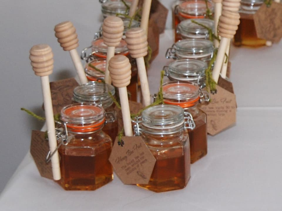 Jars our honey as wedding gifts for our guests - complete with a honey drizzle stick and our custom made hexagonal tags