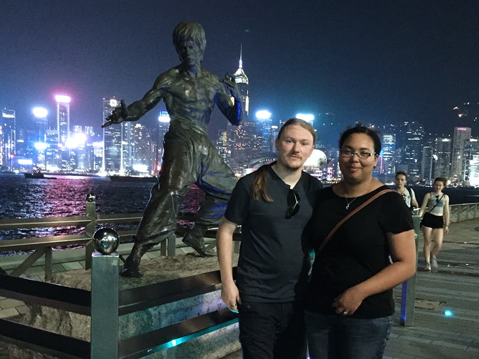 Our honeymoon in hong kong - standing next to the bruce lee statue with the hong kong city skyline in the background