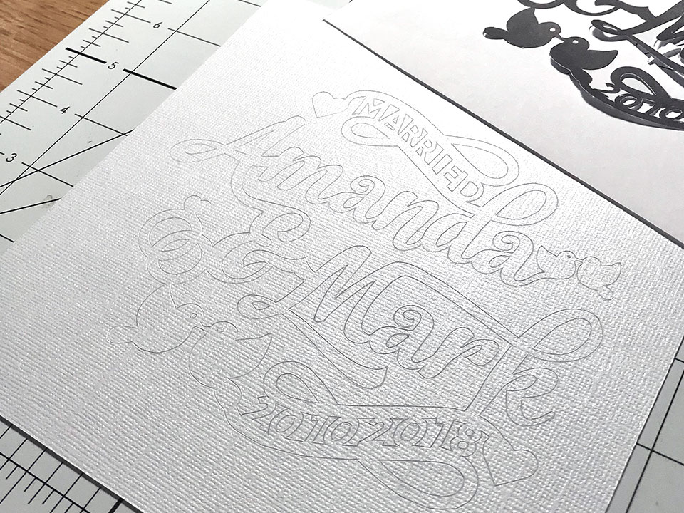 Closeup photo of the papercut design scored into white sparkly card