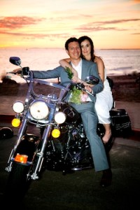Alastair and Elyse Macartney pose on a Harley Davidson  as they depart their wedding ceremony on the beach in California