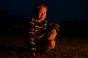 First grade portrait of a boy lit by a campfire.
