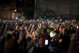 Protesters raise their cellphones in a period of silence to commemorate the lives taken by police.