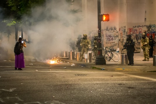 A teargas grenade goes off as Federal Police advance.