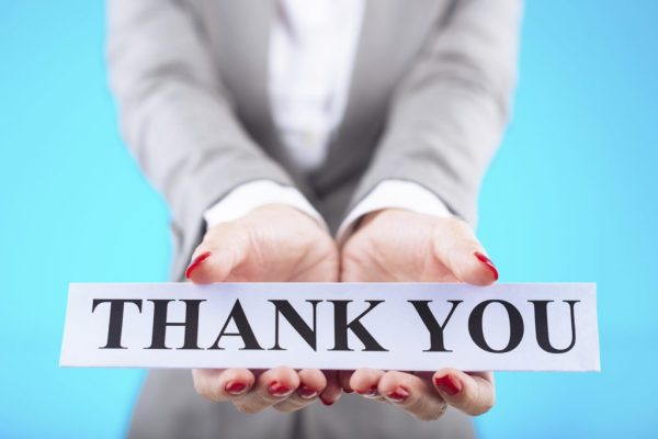 Hand of business lady showing card with thank you message