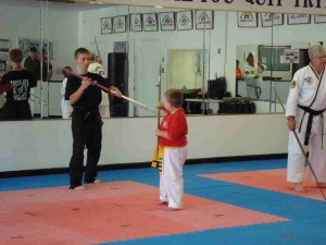 Worls Champion Tyler Giddens Assist a younger student during the leadership Jahng Bong or Bo-Staff clinic