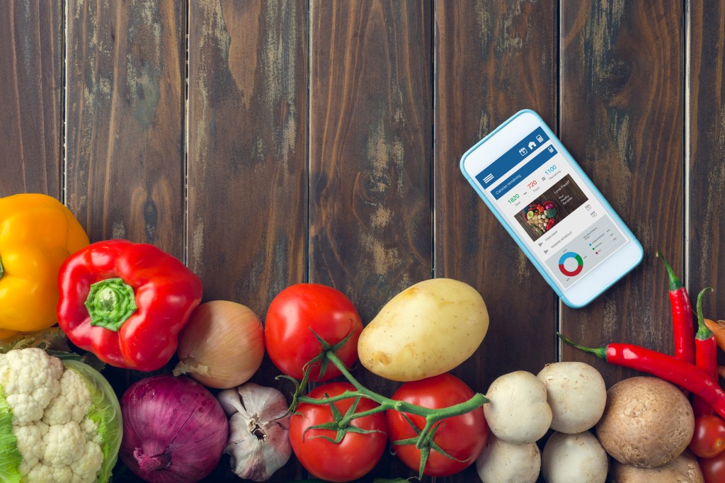 Mobile phone with food diary app. The screen shows calories remaining with a heart shape cutting board with fresh vegetables. It is on a wood table with a group of fresh vegetables.