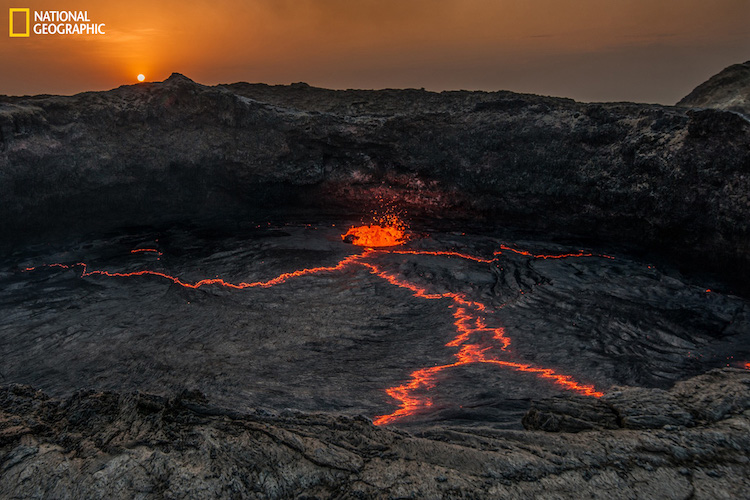 """Sunrise over the Erta Ale lava lake created a dramatic dichotomy between the power and intimidation of the angry volcano and the childlike innocence of a dancing stick-figure. The spewing and showering of molten lava, the charred, cracking of the newly formed black basalt, and the fiery sunset within the sulfuric haze created for a dramatic, ethereal experience akin to a """"gateway to hell."""" The volcano had erupted only three weeks before this image was taken."""
