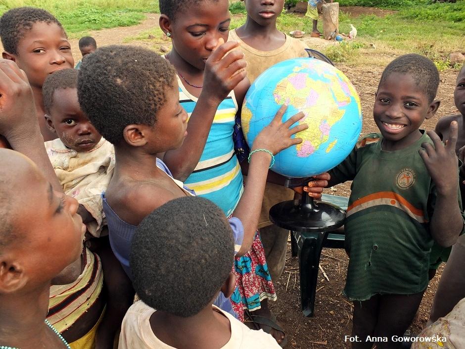 Afrykańskie dzieci z globusem podczas nauki geografii