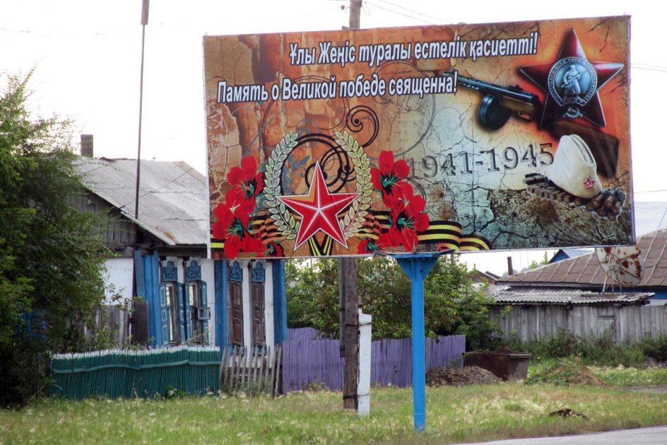 """Obwód Północnokazachstański, okolice Pietropawłowska. Propagandowy plakat wychwalający bohaterów """"wielkiej wojny ojczyźnianej""""."""
