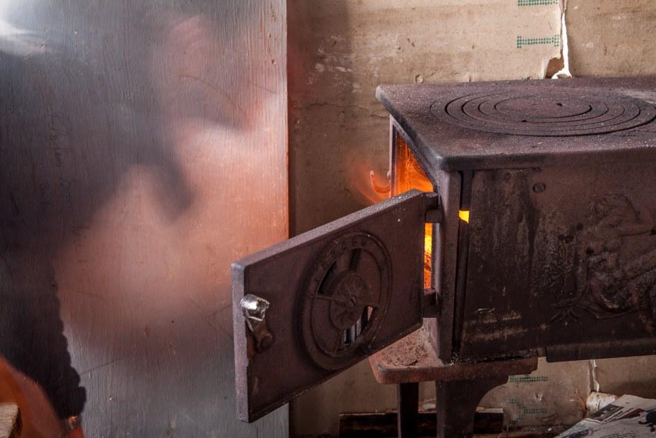 Rozpalanie pieca w fińskiej chatce. Podróż do Laponii