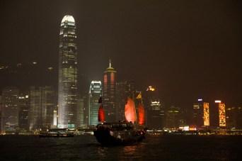 Vista nocturna de un junco atravesando Victoria Harbour, Hong Kong