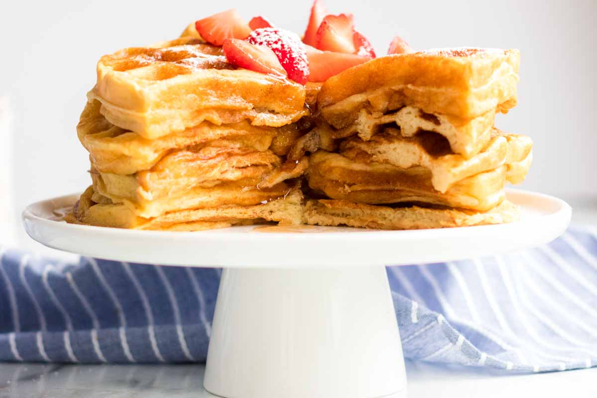 stack of 6 buttermilk waffles cut into with syrup and strawberries