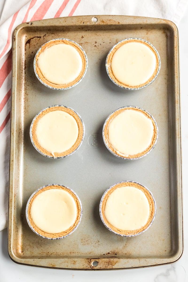 six mini cheesecakes on a baking sheet
