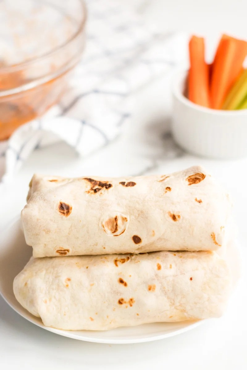 wrapped buffalo ranch chicken wraps stacked with carrots in background