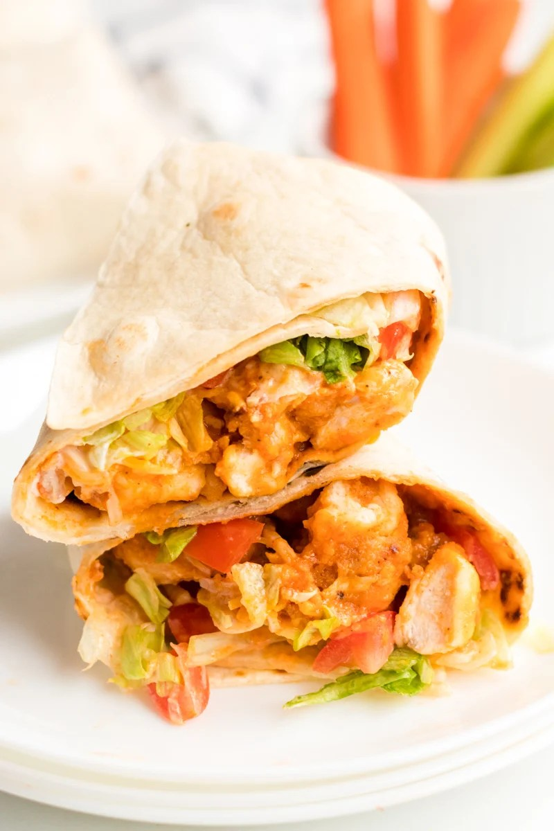 sliced & stacked buffalo ranch chicken wrap on a white plate