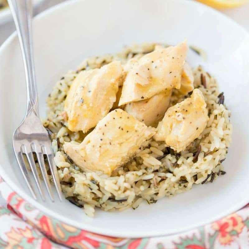 lemon chicken on a bed of rice in a white bowl with a fork