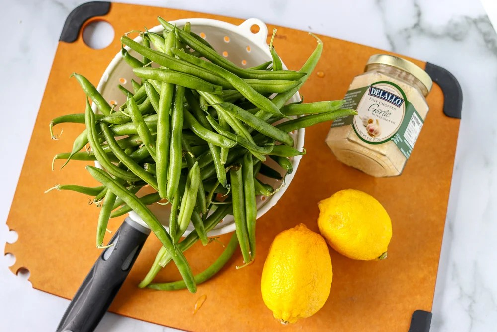 fresh green beans in colander with lemons and garlic