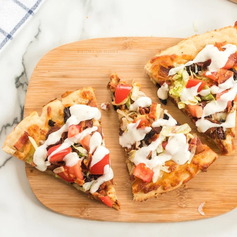 three slices of blt pizza on a wood cutting board