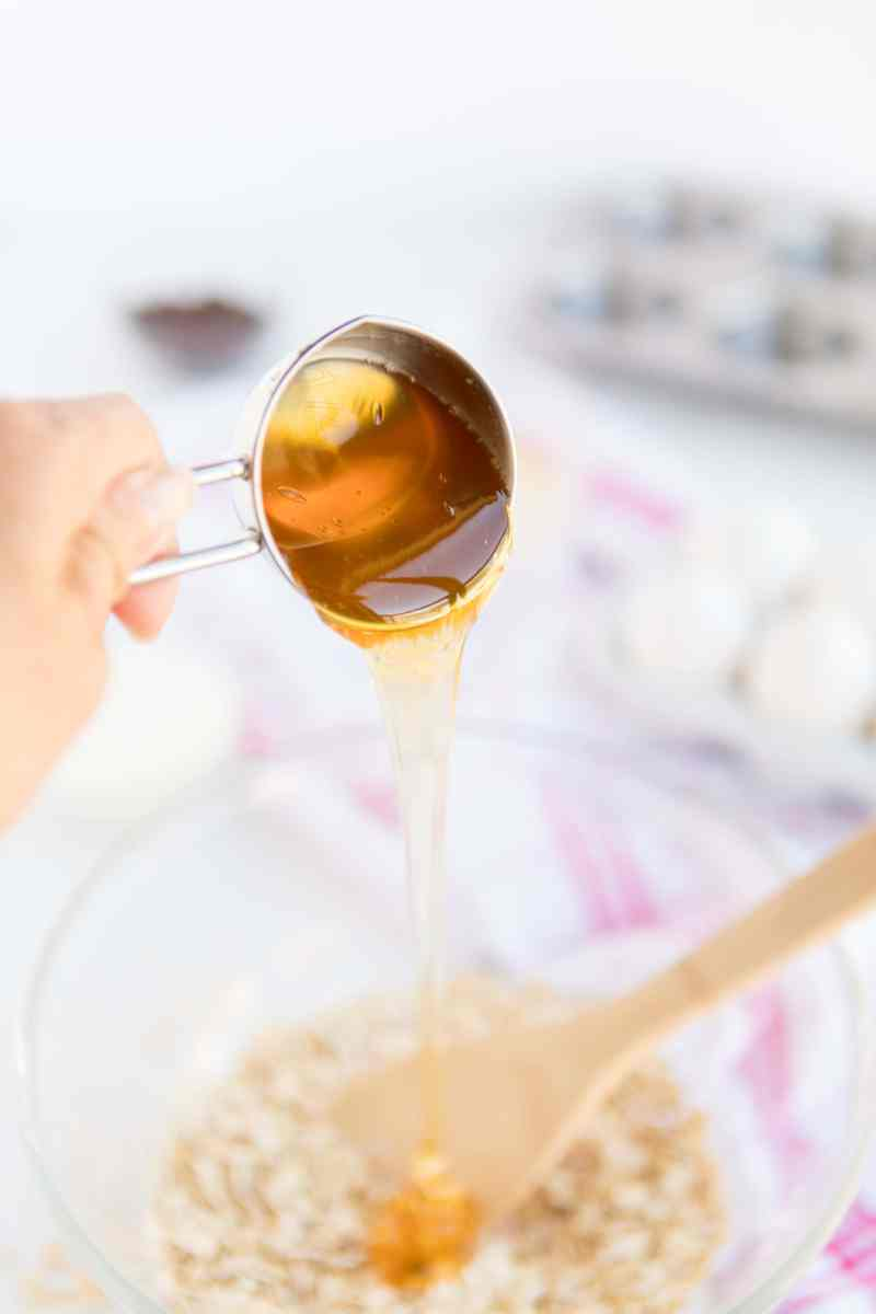 pouring honey from a measuring cup inot a bowl to make Baked Oatmeal Breakfast Cups